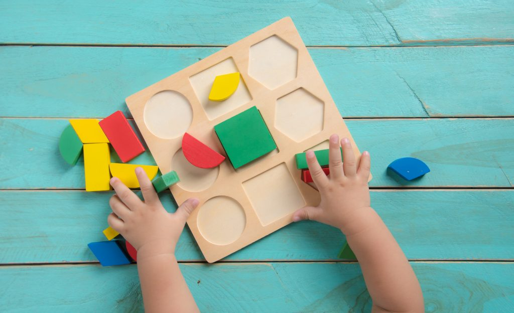 Kids playng Baby sorter with geometric figures from wood